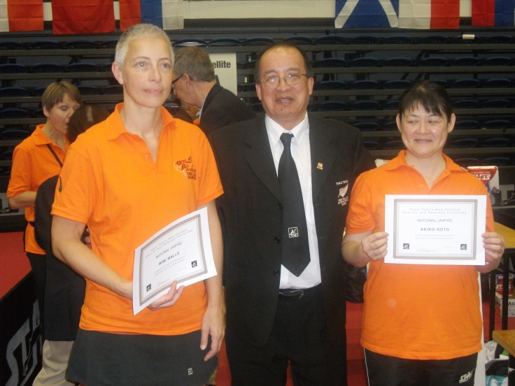 National Umpires Mimi Walle (Left) and Akiko Goto (Right) receiving their certificate from Malcolm Wong (URC).